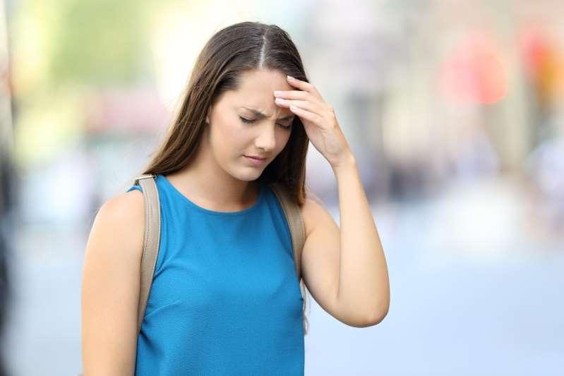 单身女人遭受头痛走在大街上